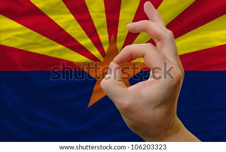 man showing excellence or ok gesture in front of complete wavy american state flag of arizona symbolizing best quality, positivity and success