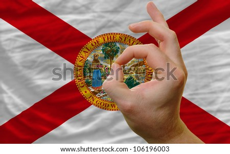 man showing excellence or ok gesture in front of complete wavy american state flag of florida symbolizing best quality, positivity and success