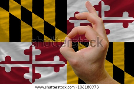 man showing excellence or ok gesture in front of complete wavy american state flag of maryland symbolizing best quality, positivity and success