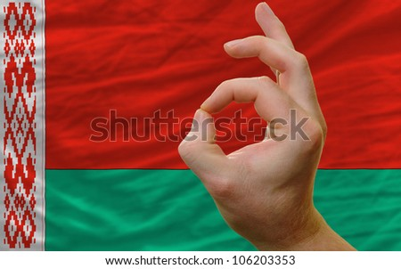 man showing excellence or ok gesture in front of complete wavy belarus national flag of  symbolizing best quality, positivity and success
