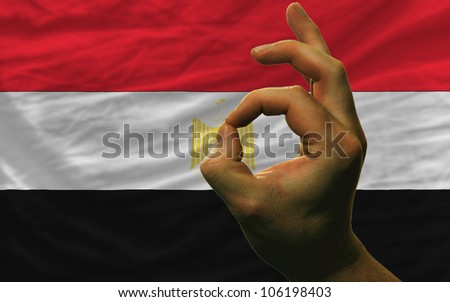 man showing excellence or ok gesture in front of complete wavy egypt national flag of  symbolizing best quality, positivity and success