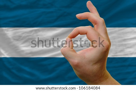 man showing excellence or ok gesture in front of complete wavy el salvador national flag of  symbolizing best quality, positivity and success
