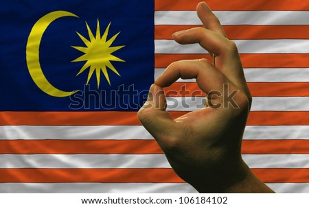 man showing excellence or ok gesture in front of complete wavy malaysia national flag of  symbolizing best quality, positivity and success