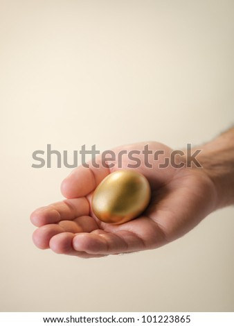 Man showing golden egg and holding it in hand. Concept of people securing savings, money, precious and valuable things, prizes. Copy space
