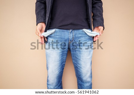 Man showing his empty pockets on cement background.