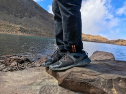 Man showing his shoes on a rock with a beautiful lake in background