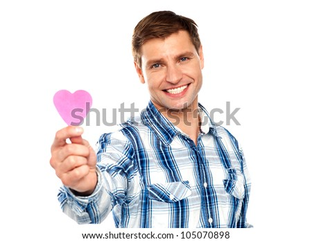 Man showing pink paper heart shaped cutting against white background - stock photo