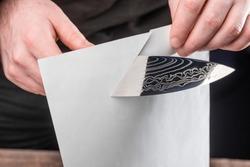 Man showing sharpness of a knife by cutting a thin paper sheet. Razor-sharp Damascus blade.