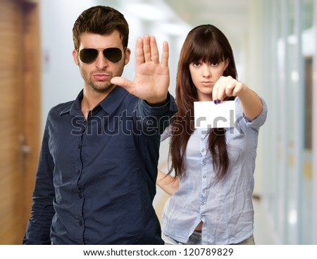 Man Showing Stop Sign In Front Of Woman Holding Placard, Indoor