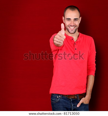 Man showing thumb up on red background