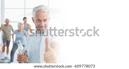 Man showing thumbs up sign with people exercising in background at fitness studio