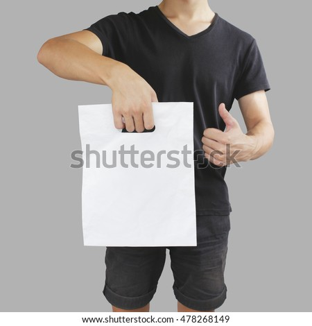 Man shows blank plastic bag mock up and thumb up isolated. Empty white polyethylene package mockup. Consumer pack ready for logo design or identity presentation. Commercial product food packet handle.
