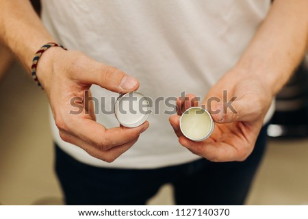 Man shows hair opened tin of hair grease.   ストックフォト ©