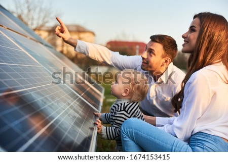 Man shows his family the solar panels on the plot near the house during a warm day. Young woman with a kid and a man in the sun rays look at the solar panels. Photo stock ©