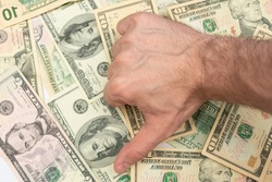 Man shows sign fiasco with thumb down, dollar bills in the background, male hand, close-up