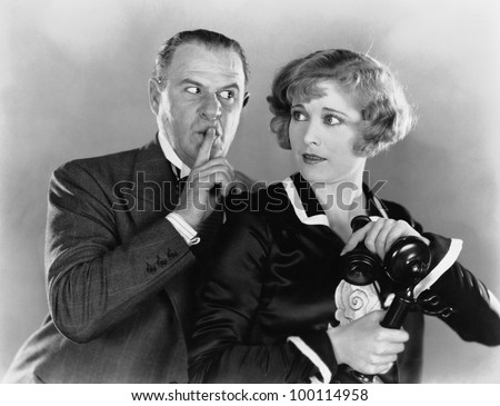 Man shushing woman on telephone