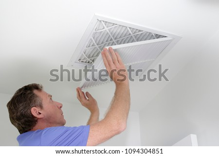 Man shutting grill of HVAC, heating ventilating and cooling after replacing the air filter. Closing ceiling grill after replacing an air filter in the ceiling.