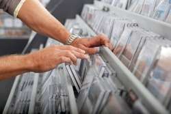 Man sifting through CDs in record shop, side view, mid-section, close-up