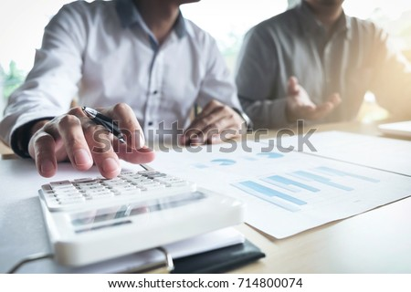 Man sign a home insurance policy on home loans, Agent holds loan investment chart graph documents and calculating table installment payment, Real Estate concept.