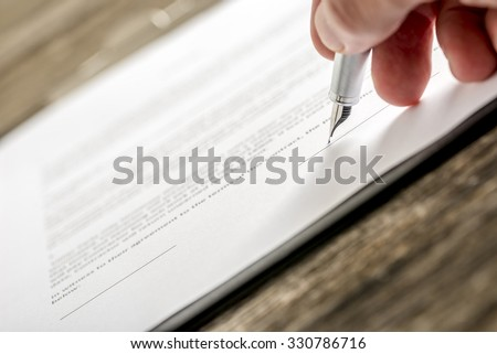 Man signing business document, application, subscription form  or insurance papers with silver pen on wooden desk.