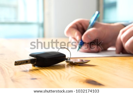 Man signing car insurance document or lease paper. Writing signature on contract or agreement. Buying or selling new or used vehicle. Car keys on table. Warranty or guarantee. Customer or salesman.