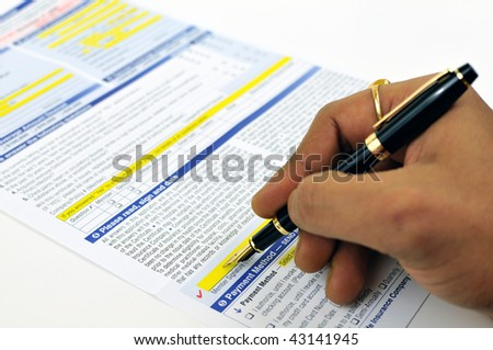 Man signing life insurance application form using a fountain pen