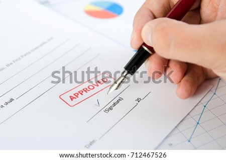 Man signs the contract with pen. Approved stamp on document. stamp approve document certificate contract agreement lawyer hand concept