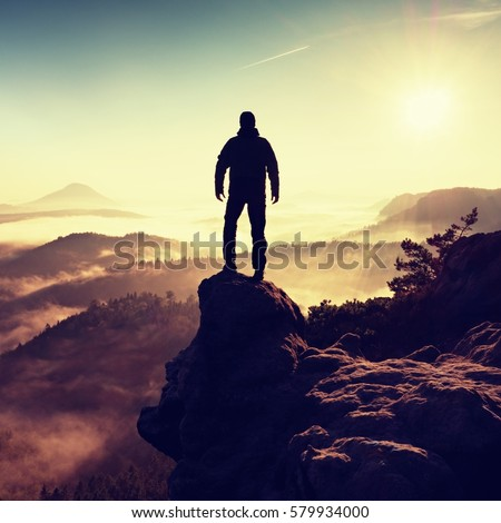 Man silhouette climbing high on cliff. Hiker climbed up to peak enjoy view. Man  watch over misty and foggy morning valley in morning Sun.  #579934000