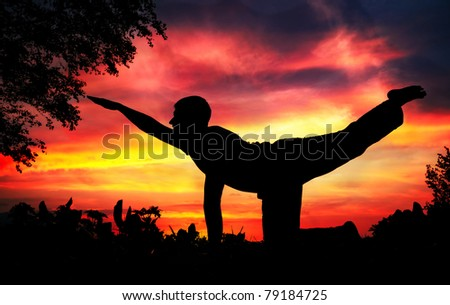 Man silhouette doing parshva marjariasana cat pose with tree nearby outdoors at red sunset background