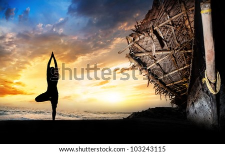 Man silhouette doing vrikshasana tree pose on the beach near the fisherman boat at sunset background in Varkala, Kerala, India