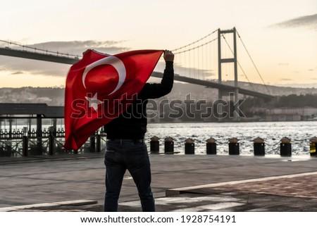 Man silhouette hold Turkish Flag in front of 15th July Martyrs Bridge (in Turkish 15 Temmuz Sehitler Koprusu ) or Bosphorus Bridge in Istanbul, Turkey. Patriotism concept.