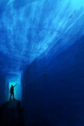 Man silhouette in ice cave. Rhone glacier, Switzerland, Europe.