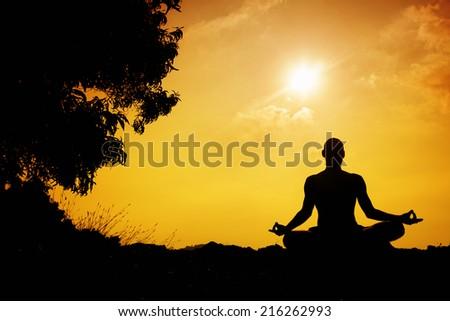 Man silhouette in Yoga meditation pose near the tree at sunset in Gokarna, Karnataka, India