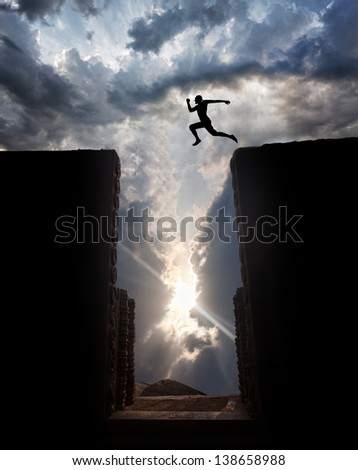 Man Silhouette jumping over the abyss at sunset cloudy sky background #138658988
