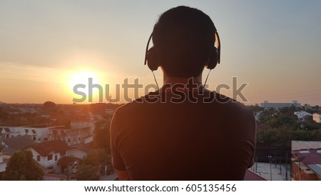 Man silhouette listening to the headphones on the sunset landscape background. - Shutterstock ID 605135456