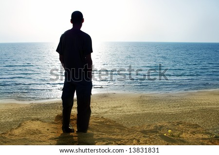 man silhouette looking at the sea
