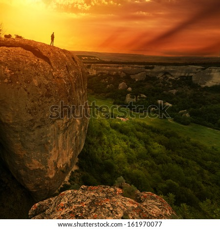 man silhouette on edge of rock with sunset sky on background