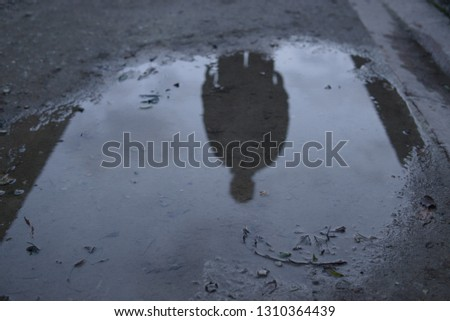 Man silhouette reflected in puddle dark reflection ominous people #1310364439