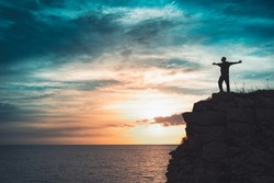 Man silhouette stands on the edge of the abyss and looks the sea with beautiful colorful sky.