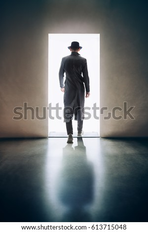 Man silhouette walking away in the light of opening door in dark room. escape concept