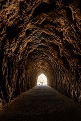 Man silhouetted with arms spread in an empty decommissioned railroad tunnel.  Taken at Blackhand Gorge State Nature Preserve in Ohio.