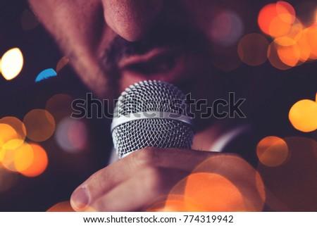 Man sings karaoke in a bar at night with festive bokeh light effect, selective focus #774319942