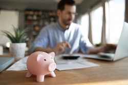 Man sit at desk manage expenses, calculate expenditures, pay bills online use laptop, makes household finances analysis, close up focus on pink piggy bank. Save money for future, be provident concept