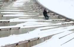 man sit blizzard. look around. alone in winter. snow around