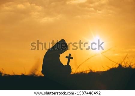 Man sit down and praying with holding the cross in hand at sunset background. christian silhouette concept.