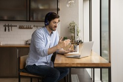 Man sit in kitchen wear headphones communicates through videoconference use laptop working remotely from homeoffice. Provide help, explanation and support to client distantly, video call event concept