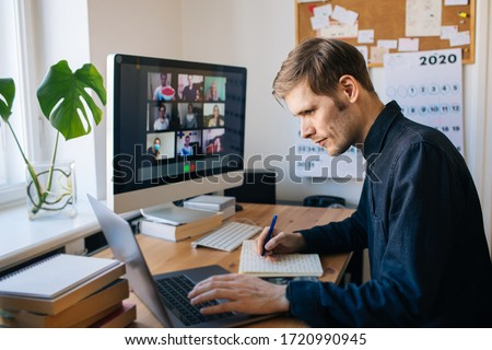 Man siting by desktop computer and making notes. Working remotely Young man having video call via computer in the home office. Stay at home and work from home concept. Managing business team meeting