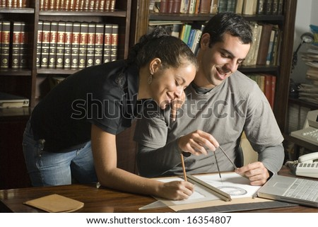 Man sits and woman leans next to him over table. There are maps and tools on the table and they are smiling. Horizontally framed photo.