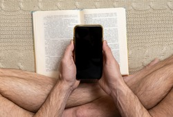 Man sits crossed legs and holding mobile phone in hands above book. Social issue of internet addiction and choice between electronic device and real book.