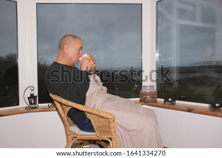 man sits in a cozy wicker chair by the wide window on the veranda, drinks tea, the concept of rest and relaxation